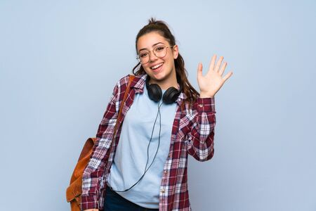 Teenager student girl over isolated blue wall saluting with hand with happy expression