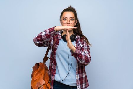 Teenager student girl over isolated blue wall making time out gesture