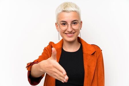 Teenager girl with short hair over white wall handshaking after good deal