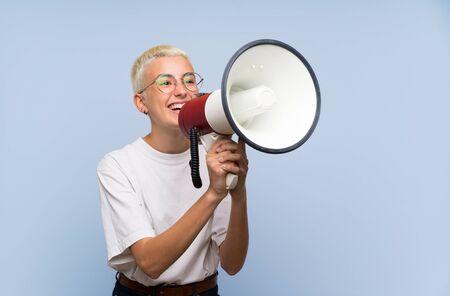 Adolescente aux cheveux courts blancs sur un mur bleu criant à travers un mégaphone Banque d'images