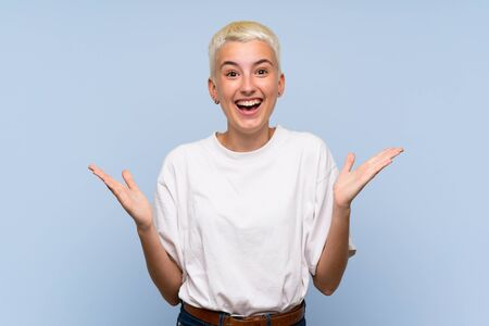 Teenager girl with white short hair over blue wall with shocked facial expression