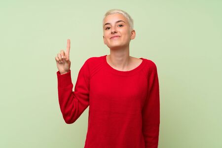 Teenager girl with white short hair over green wall showing and lifting a finger in sign of the best