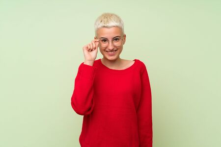 Teenager girl with white short hair over green wall with glasses and surprised