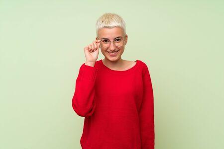 Teenager-Mädchen mit weißen kurzen Haaren über grüner Wand mit Brille und überrascht