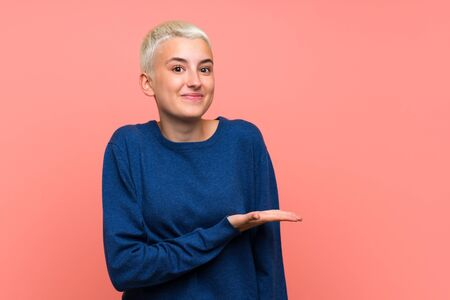Teenager girl with white short hair over pink wall presenting an idea while looking smiling towards