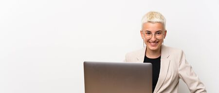 Teenager girl with short hair with a laptop posing with arms at hip and smiling