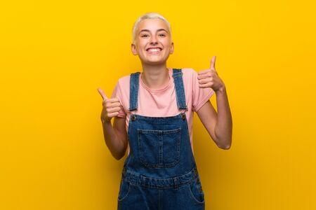 Adolescente avec une salopette sur fond jaune avec un geste de pouce levé et souriant