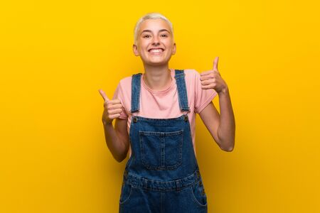 Teenager girl with overalls on yellow background with thumbs up gesture and smiling