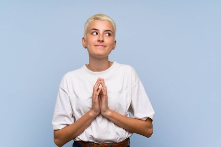 Teenager girl with white short hair over blue wall scheming something
