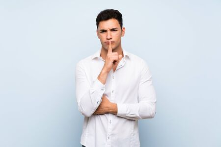 Handsome man over blue wall showing a sign of silence gesture putting finger in mouth