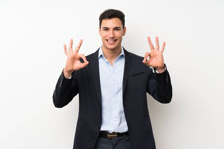 Handsome man over isolated white wall showing an ok sign with fingers