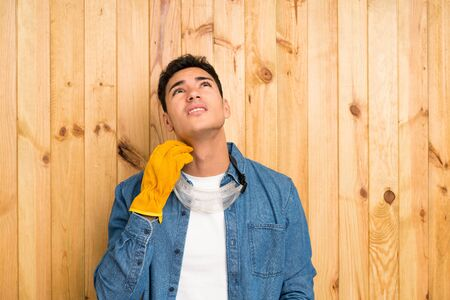 Craftsmen man over wood background thinking an idea Imagens