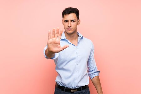 Handsome man over pink background making stop gesture