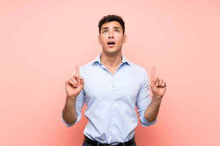 Handsome man over pink background surprised and pointing up Archivio Fotografico