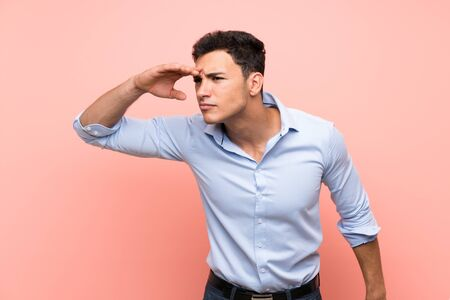 Handsome man over pink background looking far away with hand to look something