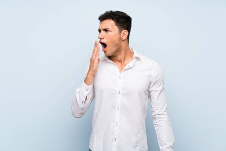 Handsome man over blue wall yawning and covering wide open mouth with hand