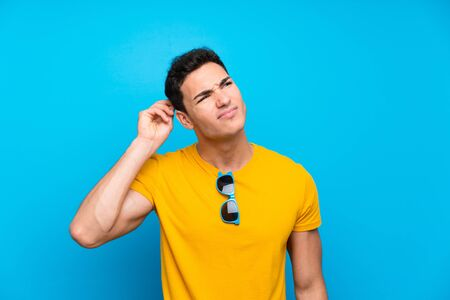 Handsome man over blue background having doubts and with confuse face expression