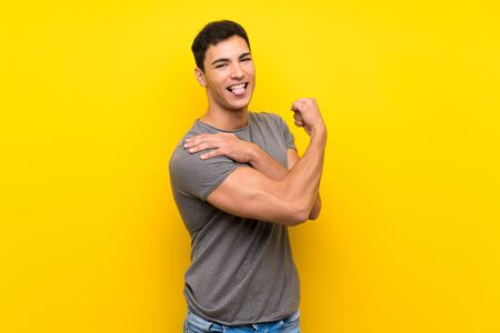 Handsome man over isolated yellow wall doing strong gesture Foto de archivo