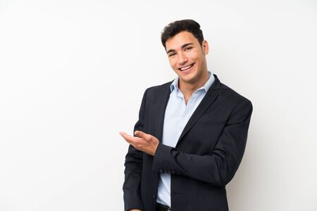 Handsome man over isolated white wall extending hands to the side for inviting to come