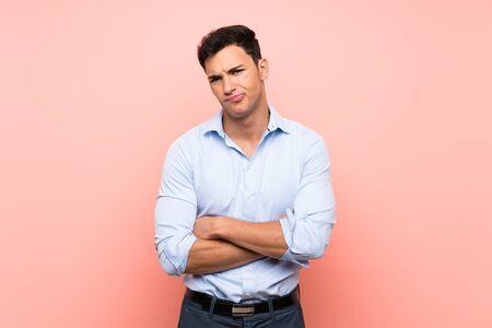 Handsome man over pink background feeling upset Standard-Bild