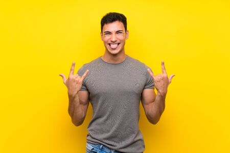 Handsome man over isolated yellow wall making rock gesture