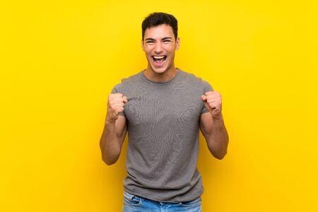 Bel homme sur un mur jaune isolé célébrant une victoire en position de vainqueur