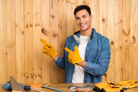 Craftsmen man over wood background pointing finger to the side
