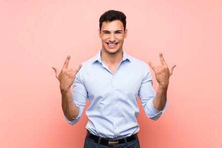 Handsome man over pink background making rock gesture