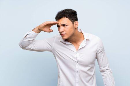 Hombre guapo sobre pared azul mirando lejos con la mano para mirar algo Foto de archivo