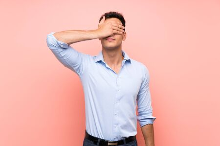 Handsome man over pink background covering eyes by hands. Do not want to see something