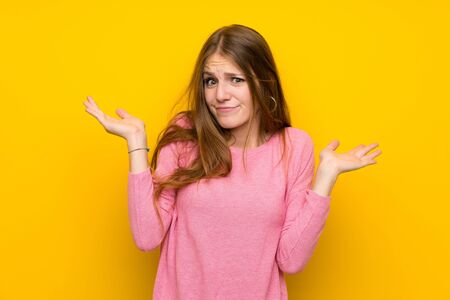 Young woman with long hair over isolated yellow wall having doubts while raising hands Stock Photo