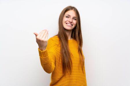Giovane donna con il giallo sopra il muro bianco isolato che invita a venire