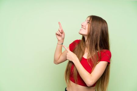 Young woman with long hair over isolated green wall pointing with the index finger a great idea
