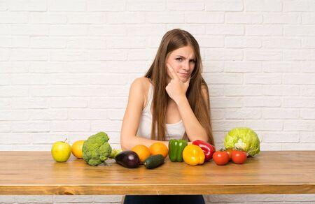 Mujer joven con muchas verduras de pie y pensando en una idea