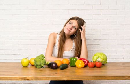 Young woman with many vegetables having doubts and with confuse face expression