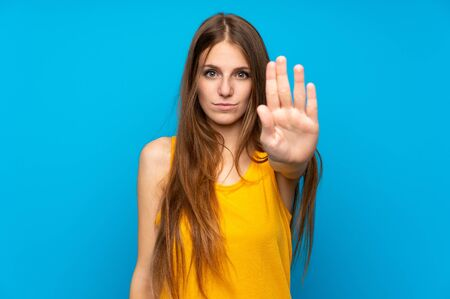 Young woman with long hair over isolated blue wall making stop gesture