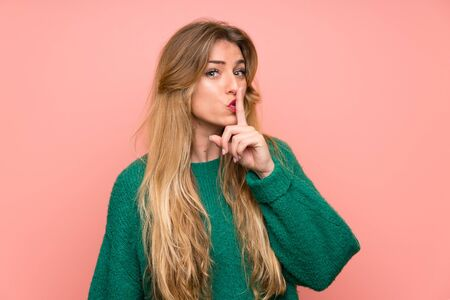 Young blonde woman with green sweater over pink wall doing silence gesture 写真素材