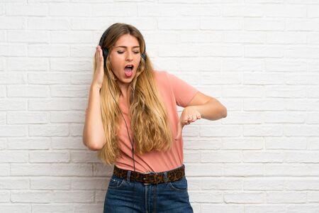 Jonge blonde vrouw over witte bakstenen muur luisteren naar muziek met koptelefoon