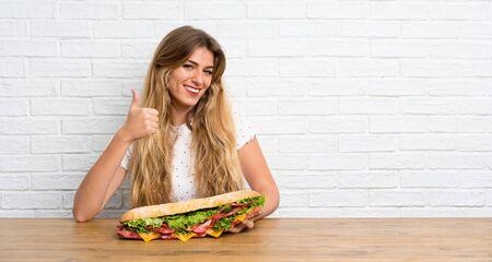 Junge blonde Frau, die ein großes Sandwich mit Daumen hoch hält holding Standard-Bild