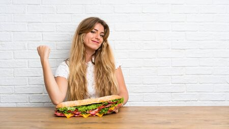 Lucky Young blonde woman holding a big sandwich Stock fotó
