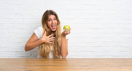 Junge blonde Frau mit einem Apfel macht Überraschungsgeste
