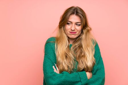 Young blonde woman with green sweater over pink wall standing and thinking an idea