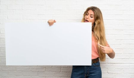 Young blonde woman over white brick wall holding an empty white placard for insert a concept
