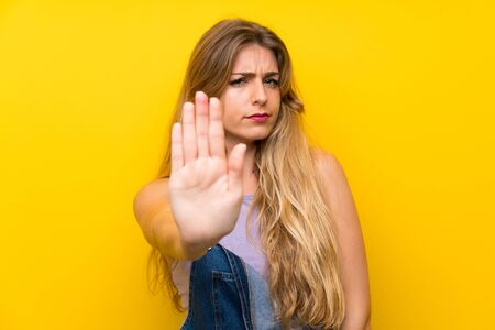 Young blonde woman with overalls over isolated yellow background making stop gesture with her hand