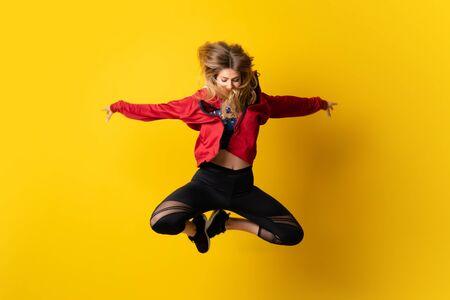 Ballerine urbaine dansant sur fond jaune isolé et sautant