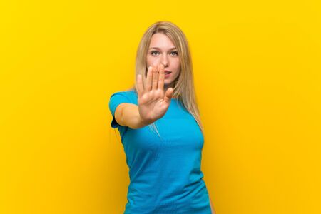 Young blonde woman over isolated yellow background making stop gesture