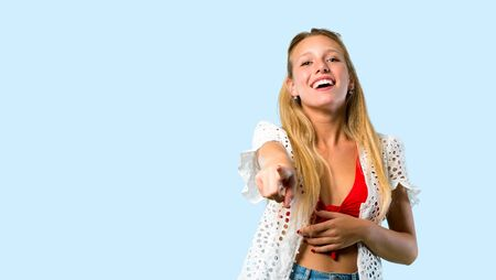 Blonde girl in summer vacation pointing with finger at someone and laughing a lot on blue background
