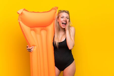 Young woman in swimsuit over yellow background shouting with mouth wide open