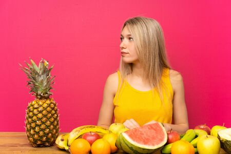Young blonde woman with lots of fruits looking side