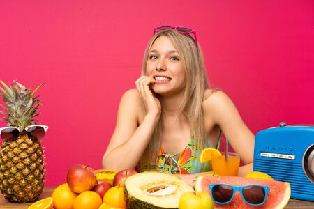Young blonde woman with lots of fruits nervous and scared 版權商用圖片